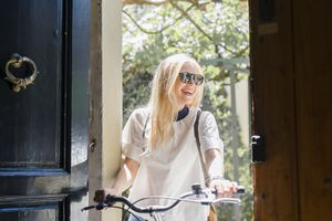 smiling woman on bicycle stands in entranceway
