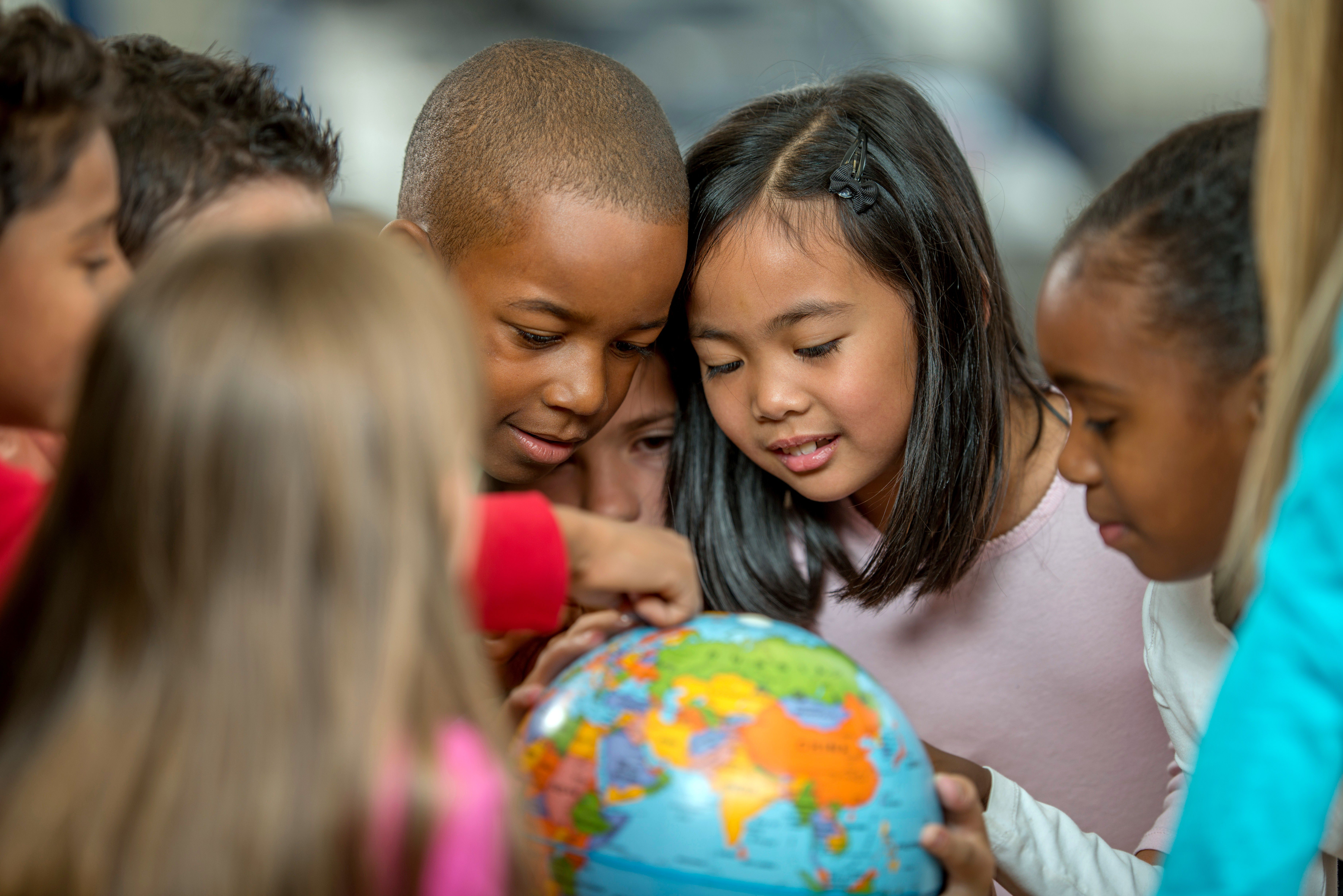 Primary school students learn about countries and geography by examining a globe