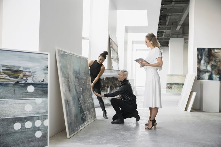 Artist and art dealers discussing paintings digital tablet