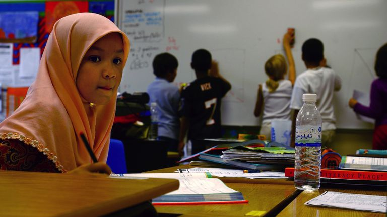 Muslim girl in classroom with students at whiteboard in the background