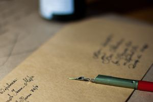 Close up of an addressed envelope with a pen sitting on top.