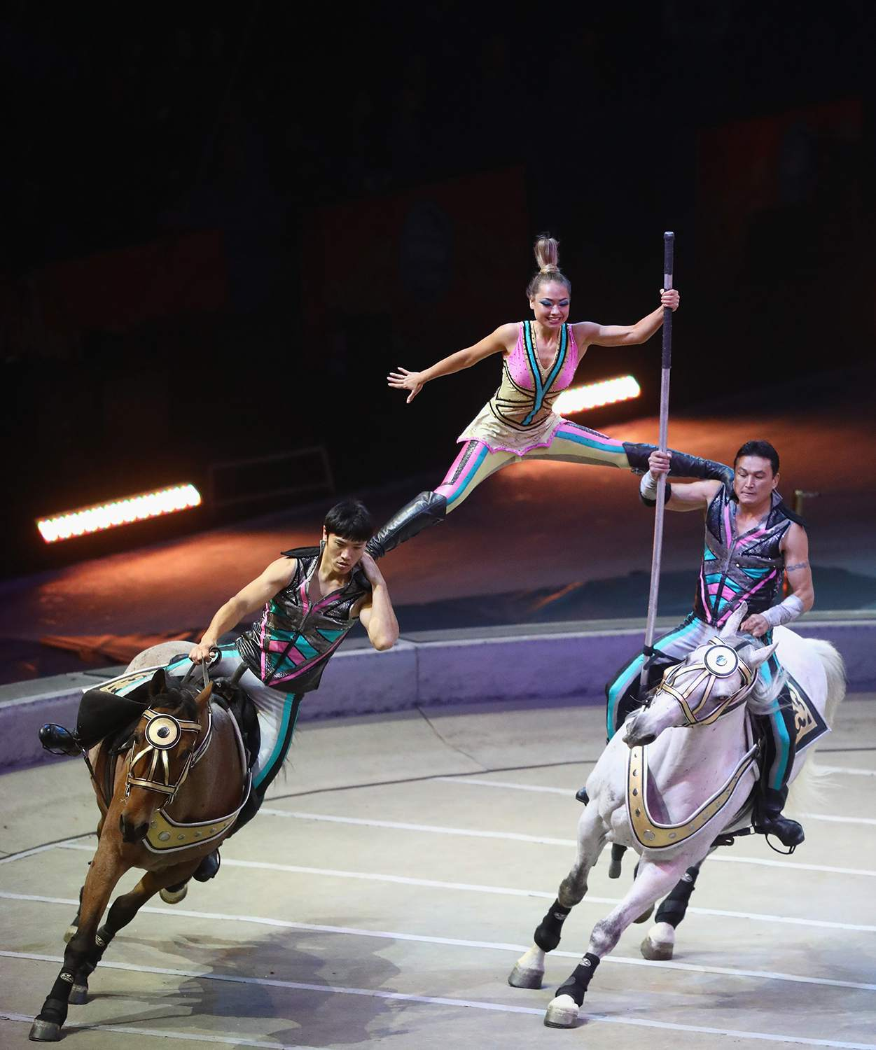 Performers during a live circus show, a woman balancing between two men riding horses.