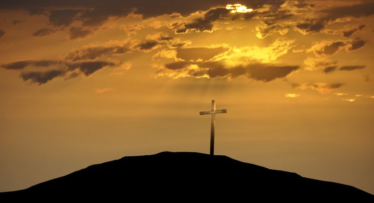 Christian Cross atop a Hill Against a Morning Sunrise