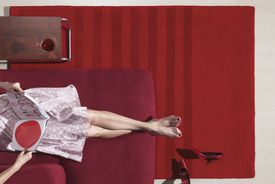 Woman relaxing on chair with magazine, low section