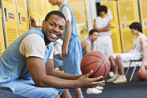 High school basketball player in the locker room with team