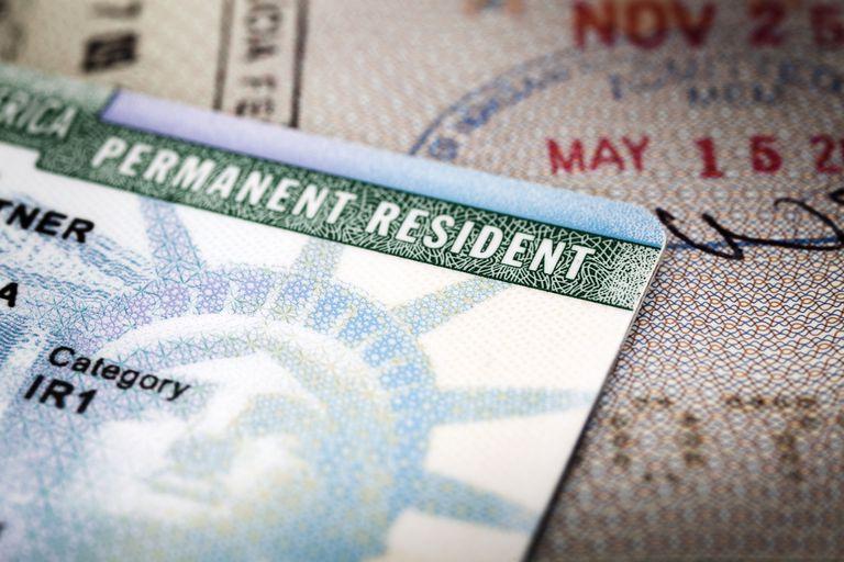 Tarjeta de residencia, también conocida como greencard, y pasaporte abierto con sello de ingreso a Estados Unidos.