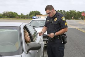Police officer examining license of young adult