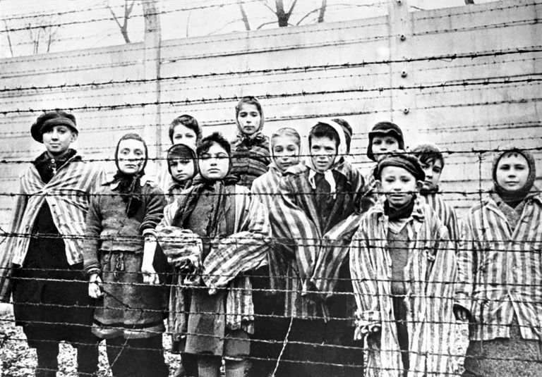 child survivors behind a barbed wire fence at the Nazi concentration camp at Auschwitz