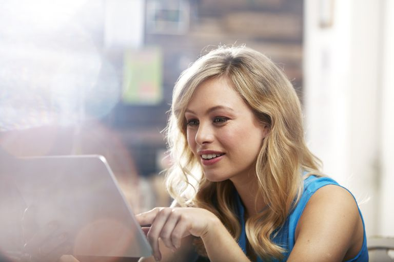 Woman using a tablet in a coffee shop.