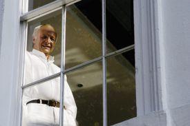 white man dressed in white seen through a window