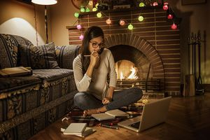 young woman studying at home sitting next to the fireplace