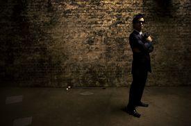 Japanese man posing as a mobster in dark alley