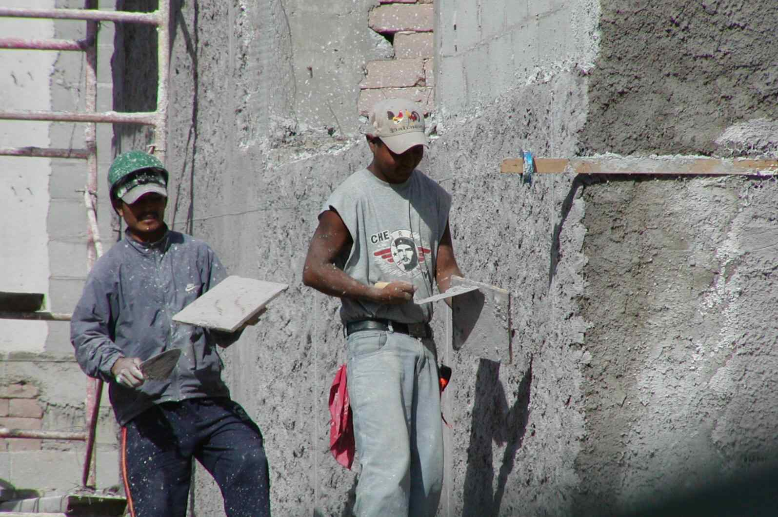 two workmen applying a layer of plaster with trowels