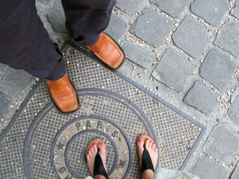 Downward view of a man's and woman's feet as they stand on a Paris street