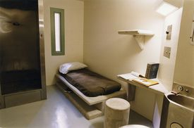 A bed, desk, and sink in prisoner's cell