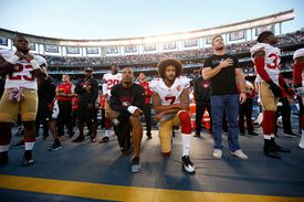 Photograph of Colin Kaepernick of the San Francisco 49ers kneeling during the national anthem.