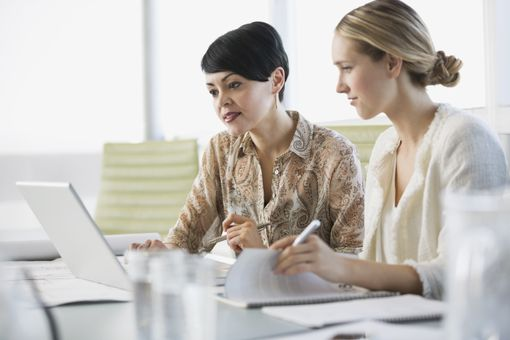 Businesswomen working on laptop together