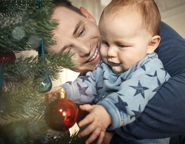 father and baby looking at christmas tree 577291673 57f2fd213df78c690f691d67 jpg