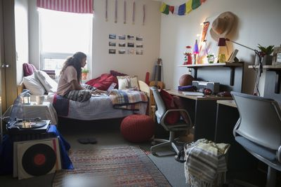 Female College Student Studying At Laptop On Bed In Dorm Room