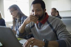 Focused adult education student using laptop