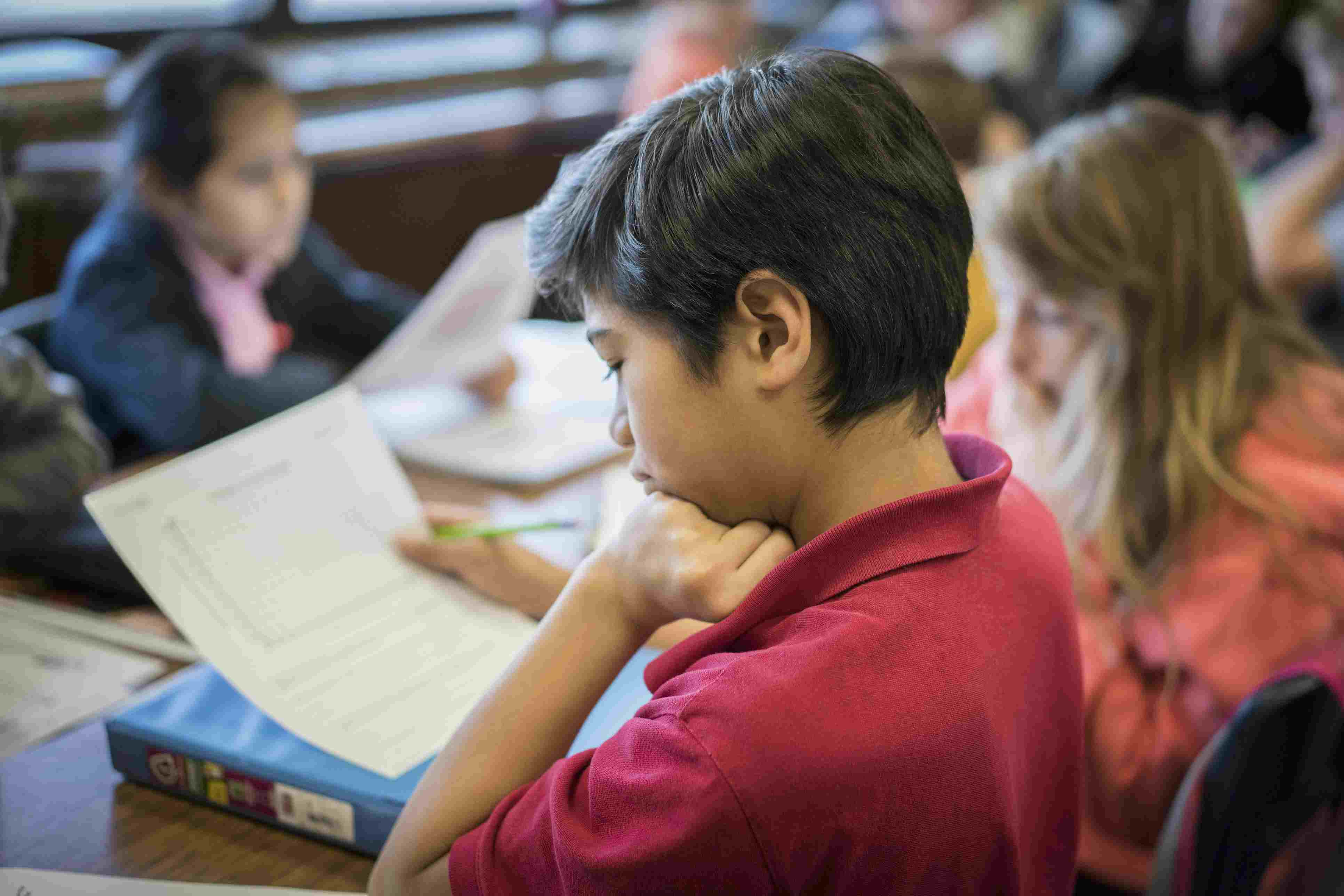 Student reading paper at desk in classroom