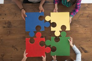 People of different races work together to assemble a puzzle, symbolizing the concept of social order.
