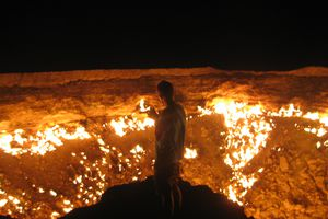 Man standing in front of the Gates of Hell, at Derweze, Turkmenistan.