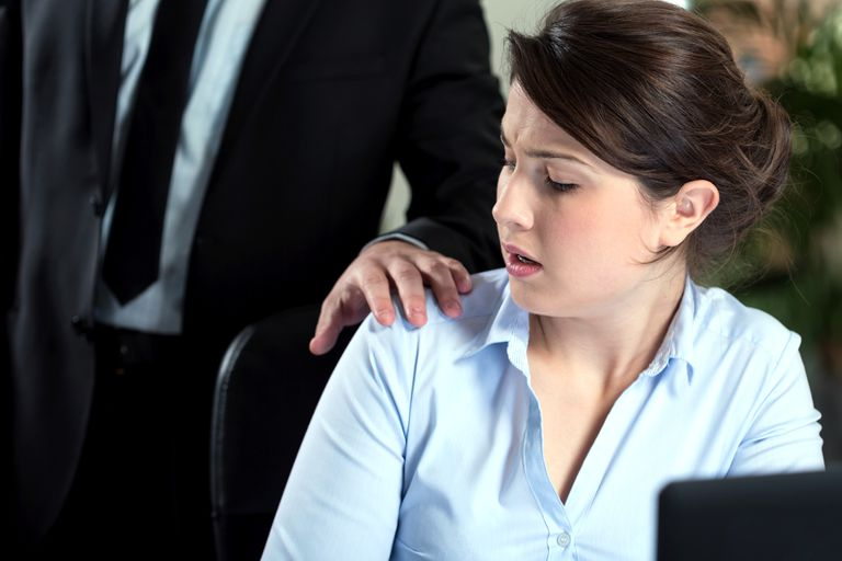 A male coworker places an unwelcome hand on a woman's shoulder