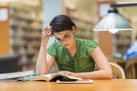 Woman studying with book in the library
