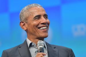 Barack Obama holding a microphone and smiling.