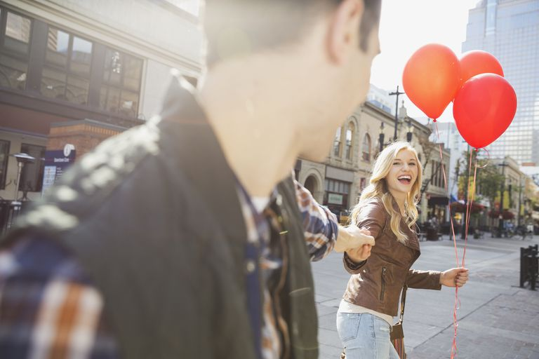 A couple with red balloons holds hands