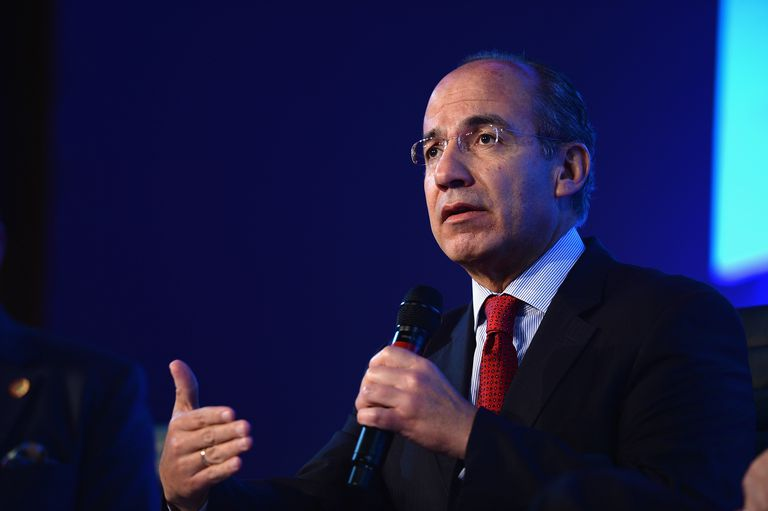 Felipe Calderón holds a microphone while addressing an audience