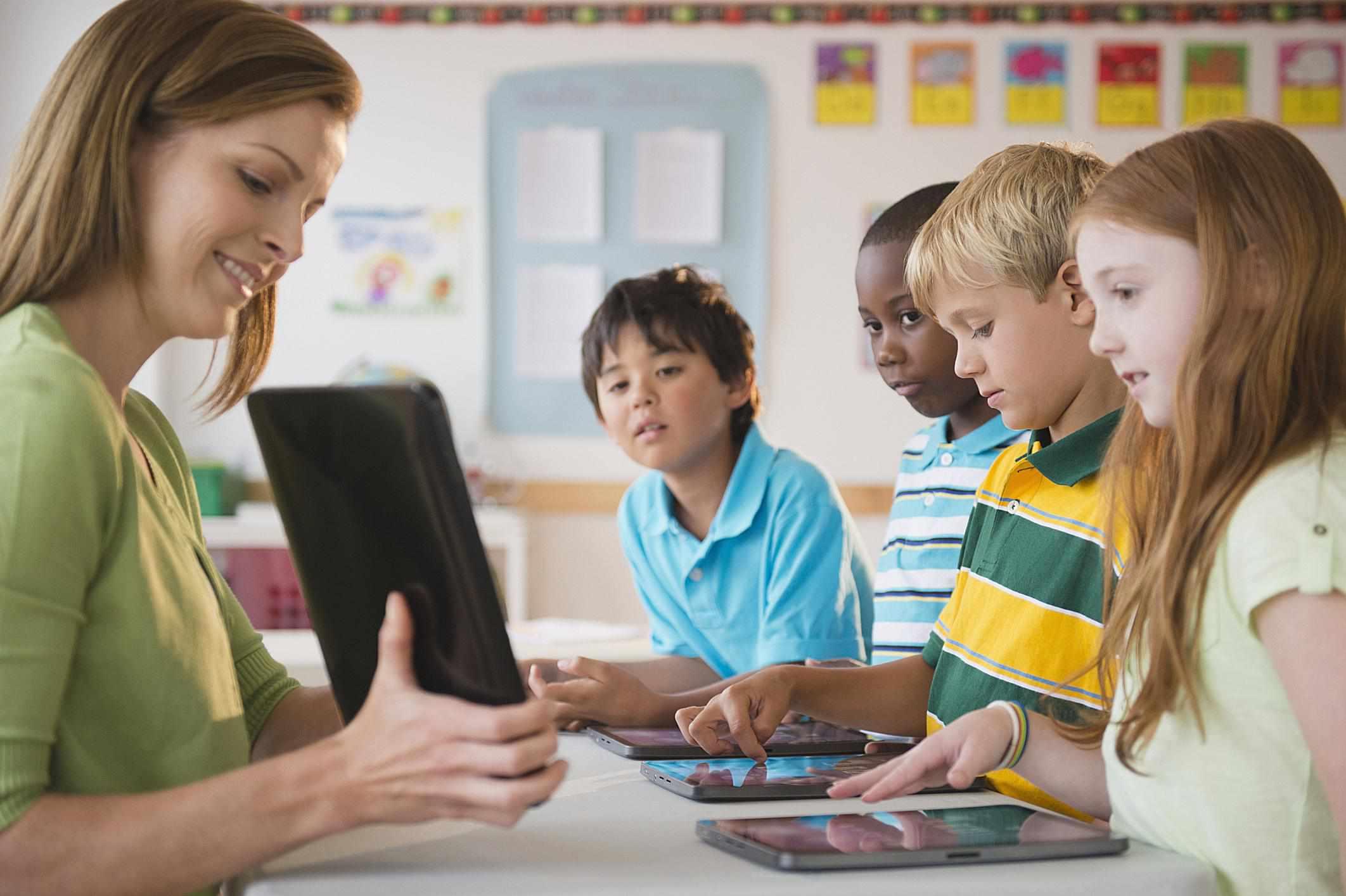A teacher showing children a tablet