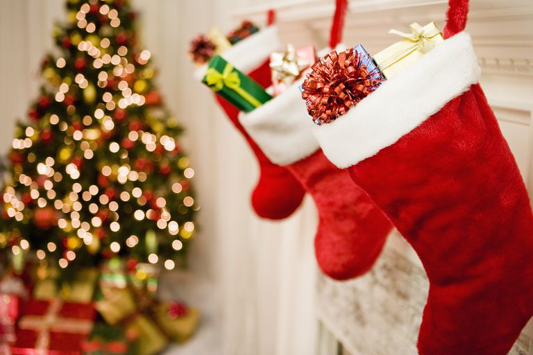 stuffed Christmas stockings hanging above fireplace