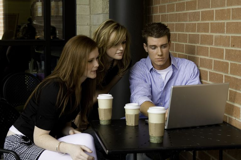 Three people in a coffee shop looking at a laptop together