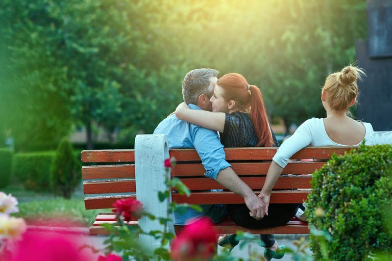 man on park bench hugs one woman while holding hands with another