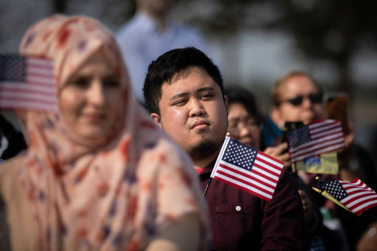 people holding flags at naturalization ceremony