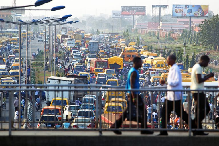 Three men cross a bridge over Lagos traffic. Is Africa Overpopulated?
