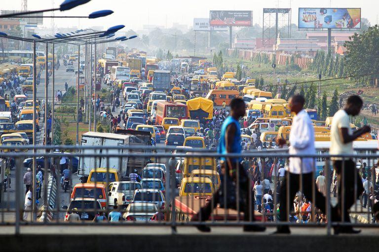 Three men cross a bridge over Lagos traffic. Is Africa Overpopulated?
