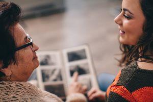 Grandma showing photo album to granddaughter.
