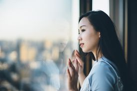 An Asian woman looks outside a window at the city below her, signifying the distinction between the private and public spheres of social life.