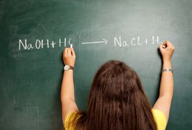 Woman Writing a Chemical Equation on a Chalkboard