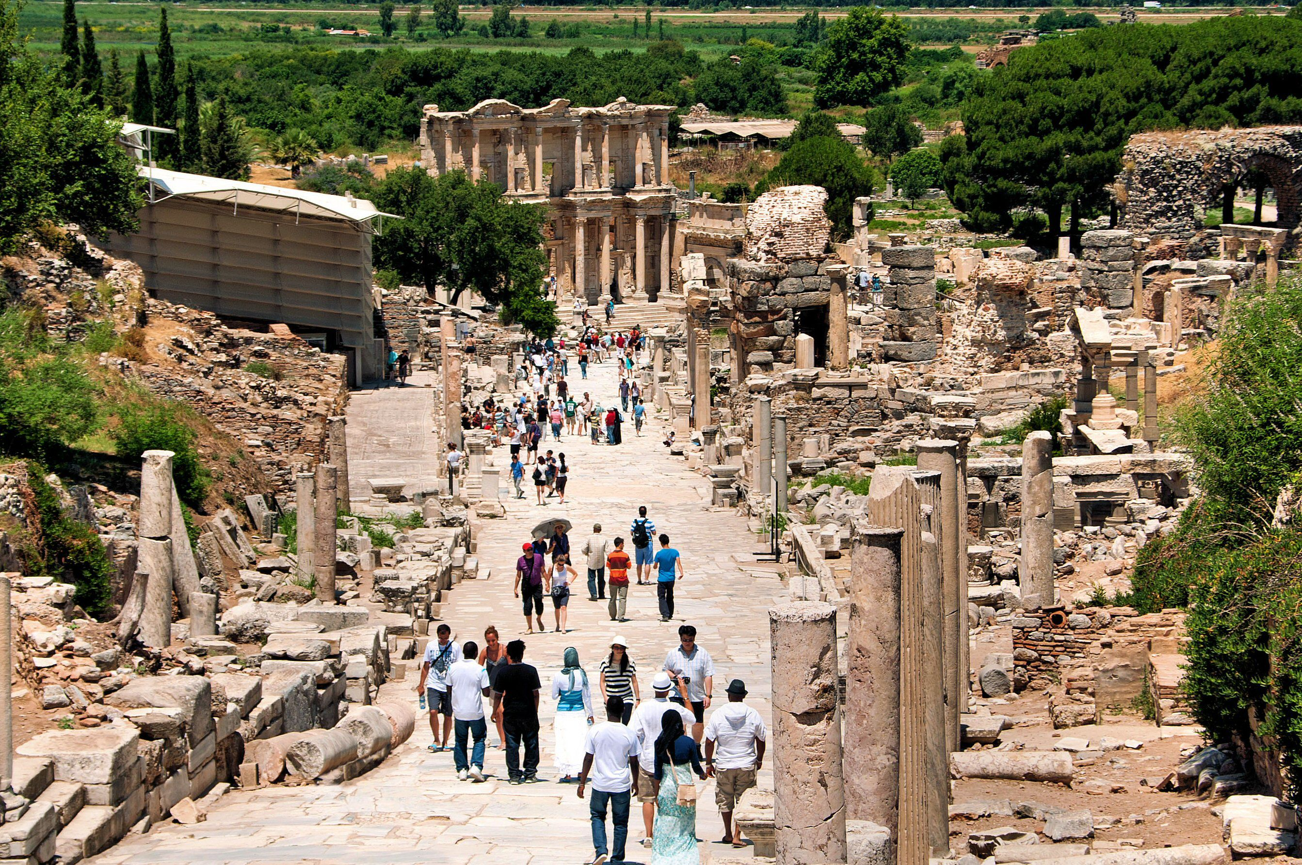 high angle looking at people walking amongst stone ruins of ancient architecture