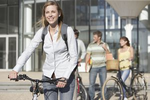 Young woman with bicycle with students in background