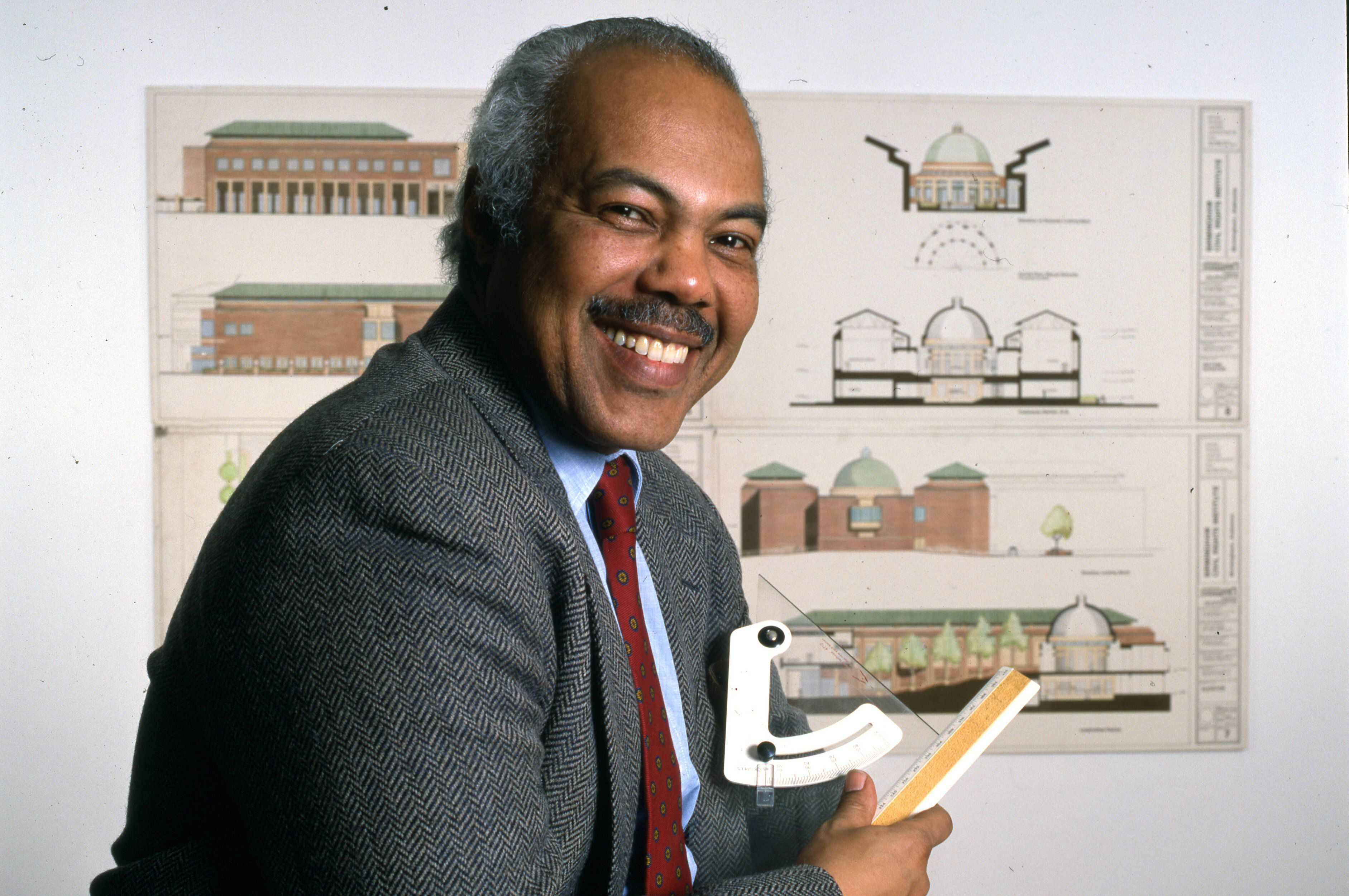 Black man in suit, smiling, posing with architecture sketches and tools