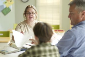 Parent Teacher Meeting with teacher talking to student and parent