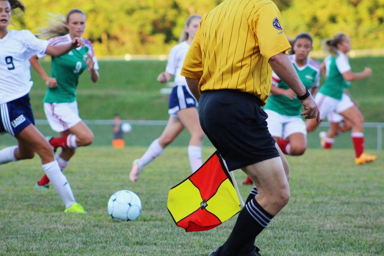 Soccer game in action with referee on the field.