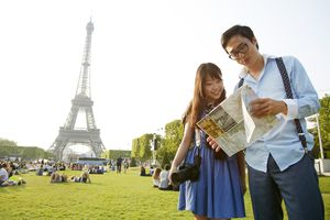 Young couple looking at map near the Eiffel Tower