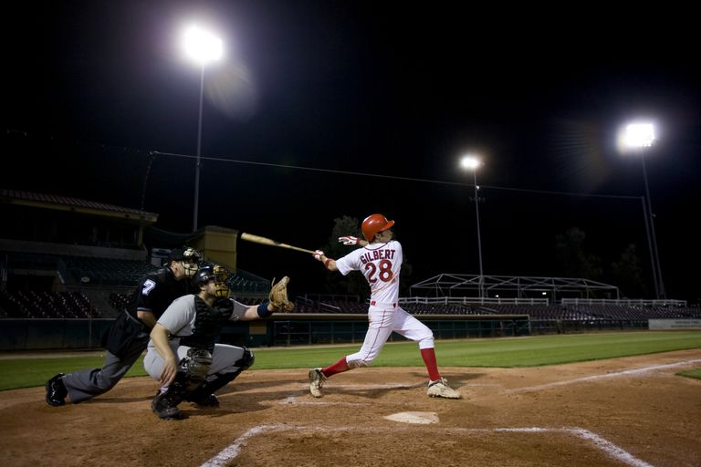 A baseball player swings for a pitch during a night game