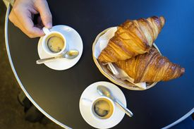 Espresso and croissants on round table